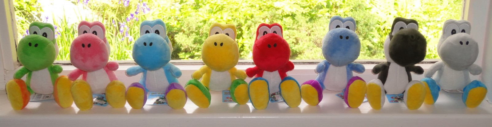 Row of Yoshi plushies on a windowsill
