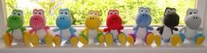 Row of Yoshi plushies on a windowsill