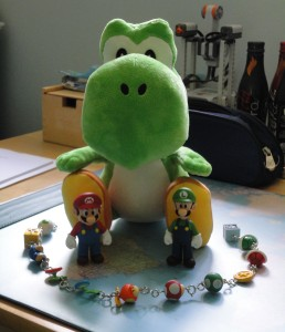 A Yoshi plushie towers over the figures of Mario and Luigi, surrounded by their power-ups